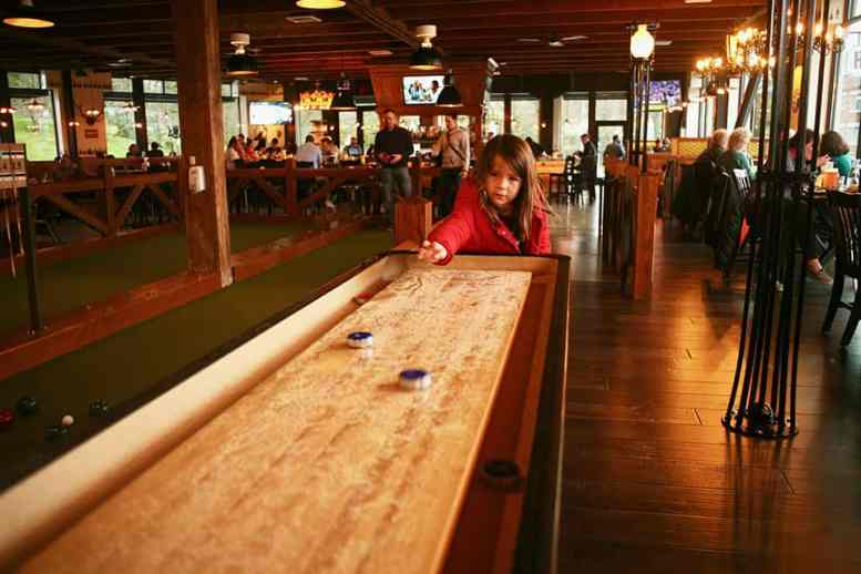 Ruby plays shuffleboard inside the restaurant