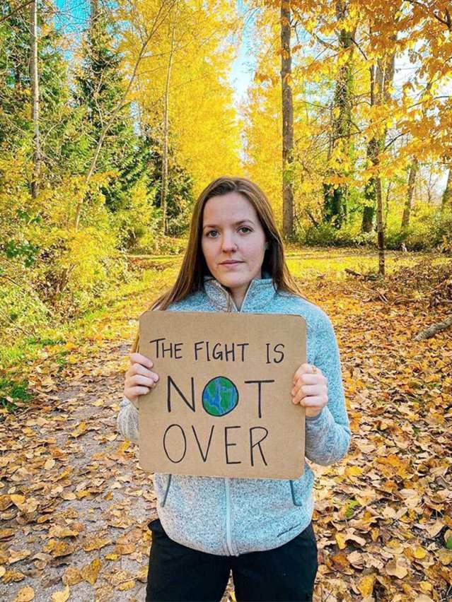 """A woman stands in a forest with a sign that reads, """"The fight is not over."""""""