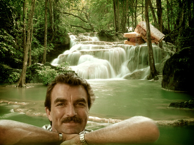 Tom Selleck hanging out with a sandwich in a waterfall.