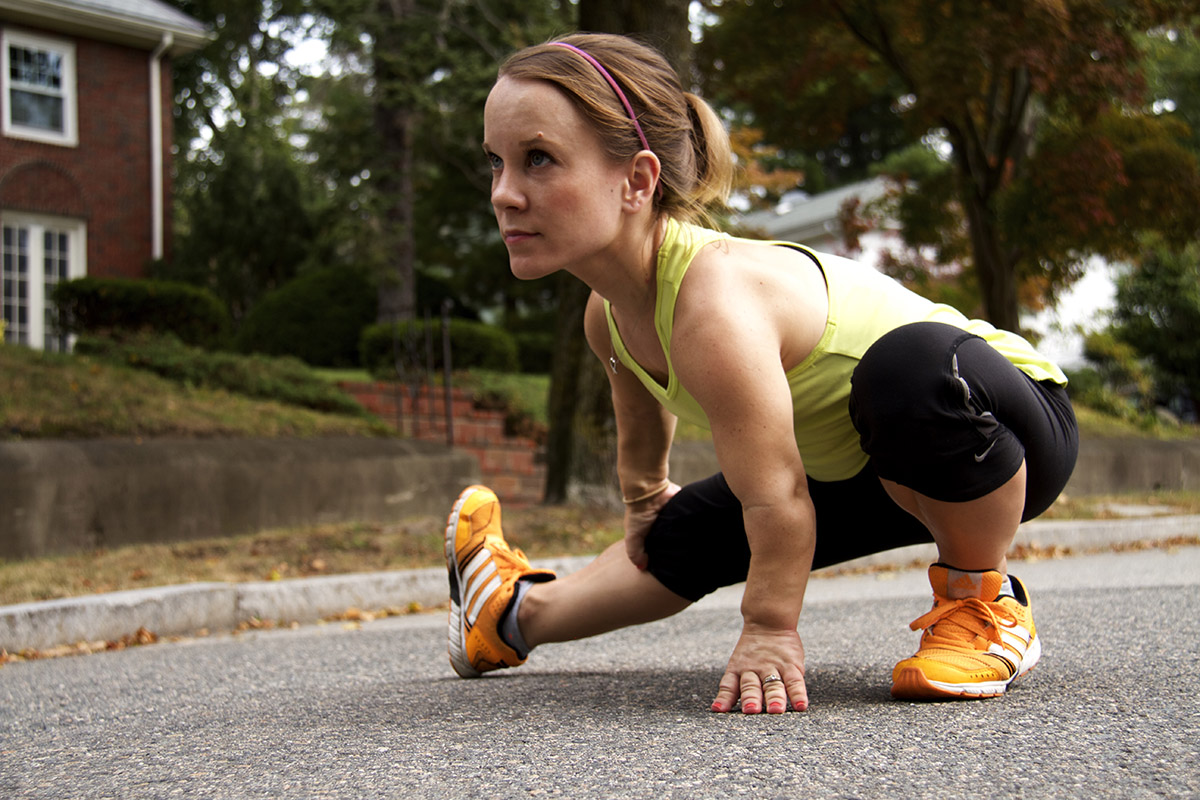 A woman with dwarfism, a condition that results in short stature, is dressed in athletic clothes. She is stretching on a residential street, preparing for a run