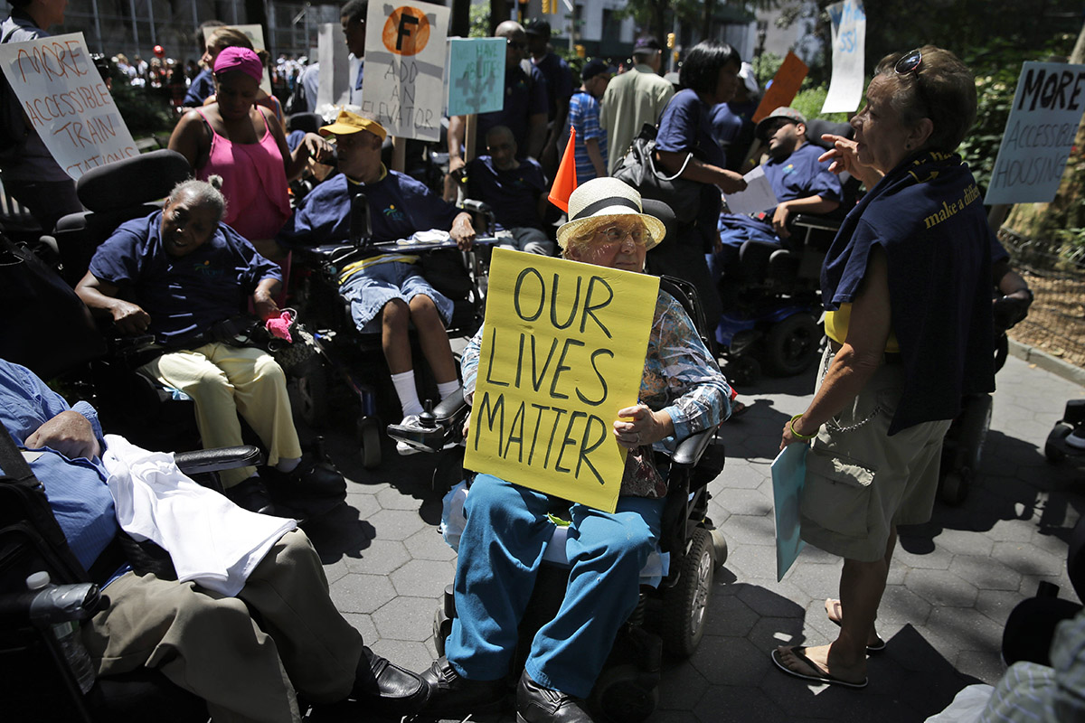 "Anita Cantor, in a wheelchair, holds a sign that reads ""Our Lives Matter"" during the inaugural Disability Pride Parade in New York. Around her, other with disabilities hold signs calling more elevators at train stations and more accessible housing"