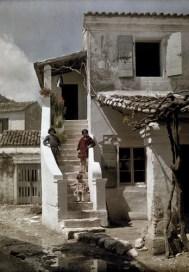 Κορίτσια στέκονται σε σκάλα σπιτιού που βρίσκεται σε κερκυραϊκό ψαροχώρι.