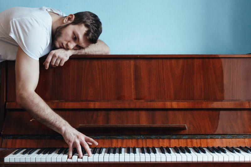 Homme allongé sur un piano