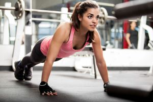 Young woman doing push ups in a gym.
