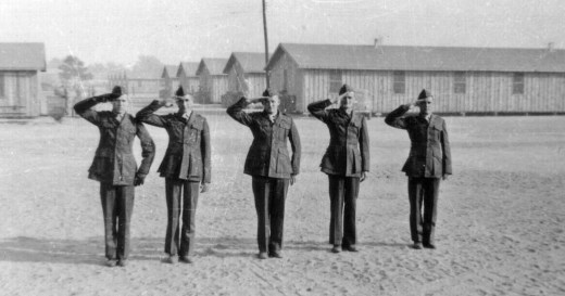 """Snap a salute with a """"seabag crease"""" in their trousers, these Marines report for KP following their trip to the rifle range."""