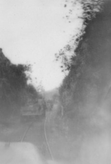 Passing through a narrow cut along the railway line.