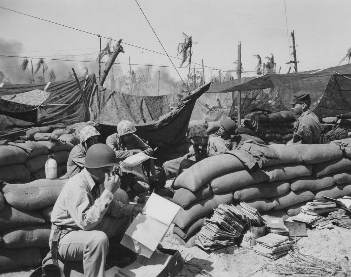The R-2 section of the 24th Marines examines a haul of Japanese documents. Man at right is wearing a Japanese cap.