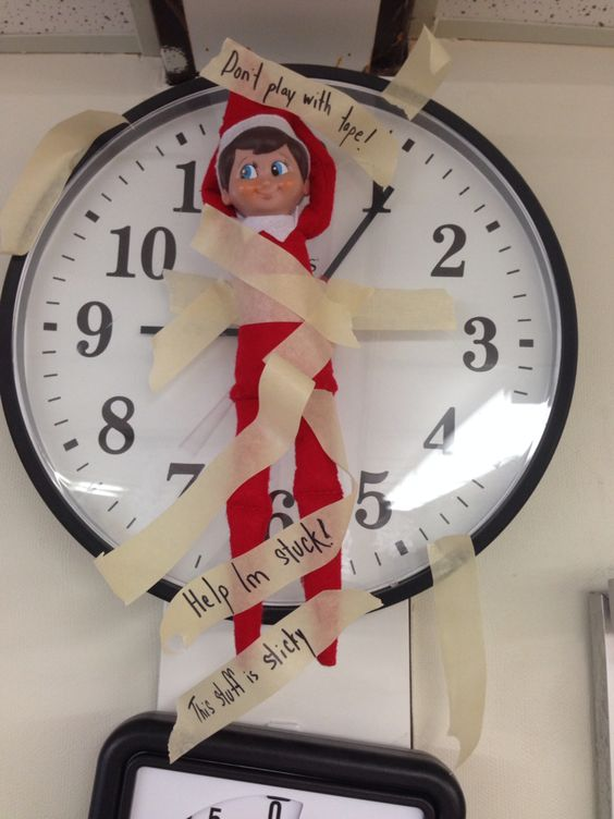 Elf on the Shelf taped to classroom clock.