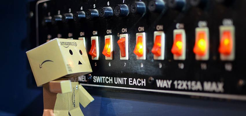 A cardboard robot looking at a series of switches.