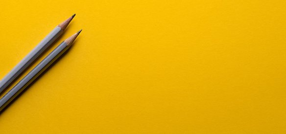 Gray pencils sitting on a yellow background.