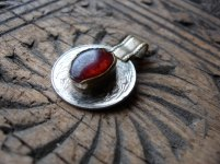Photo of a kuchi coin pendant with a red oval stone