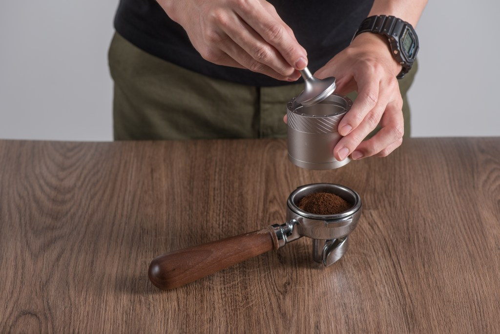 Barista releasing coffee ground from the magnetic catch-cup oi JE-Plus grinder