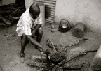 Father Fanuel prepares morogo, a kind of wild green, over an open fire in the backyard.