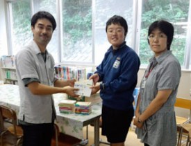 NICCO staff presents books to a junior high school that had been damaged in the disaster.