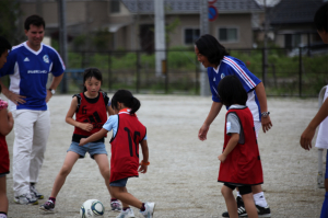 Professional soccer player Tsuyoshi Kitazawa coaches kids in Natori at a NICCO-sponsored event.