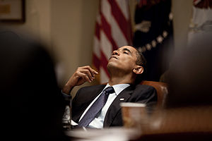 English: President Barack Obama leans back in ...