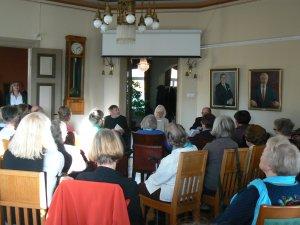 Claes Andersson, Birgitta Ulfsson och Jacob Söderman pratar om Atos Wirtanen i Gamla stadshuset. Foto: Minkki Huldén