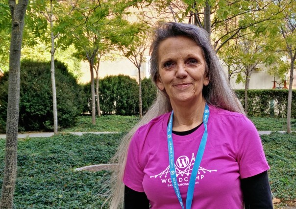 Kim Parsell, a smiling woman with long gray hair in a pink WordCamp San Francisco volunteer t-shirt, standing outside among trees.
