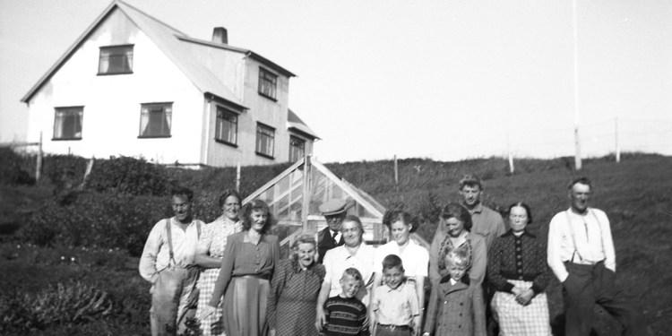 Heimilisfólkið á Hólum stendur við gróðurhúsið í garðinum. Íbúðarhúsið sést uppá hólnum