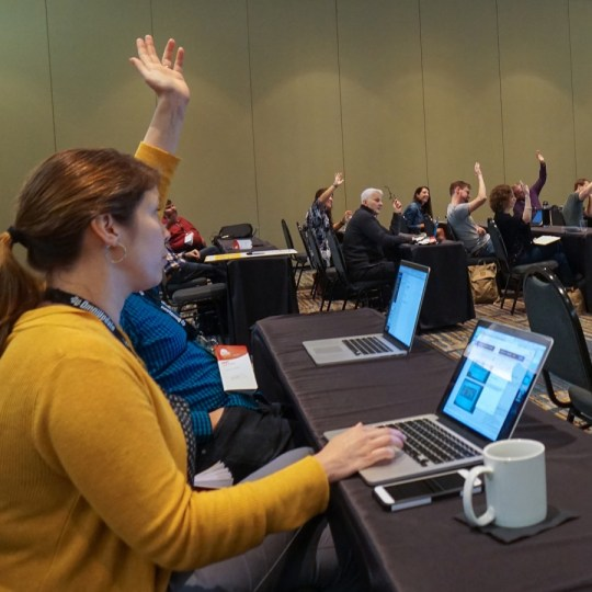 Workshop attendees raising their hands.
