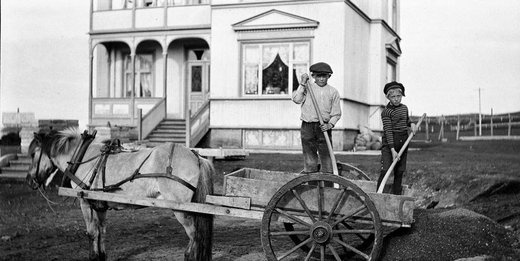 Tveir drengir á hestakerru í garðinum við hús Gísla J. Johnsen, Breiðablik. Drengurinn til hægri er Gísli friðrik Johnsen (1906-2000), sonur Gísla J. Johnsen, fæddur 1906.