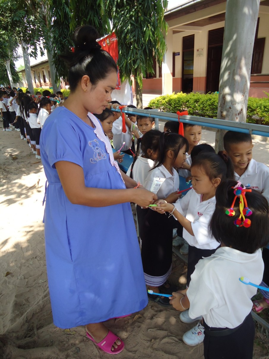 A teacher distributes toothpaste