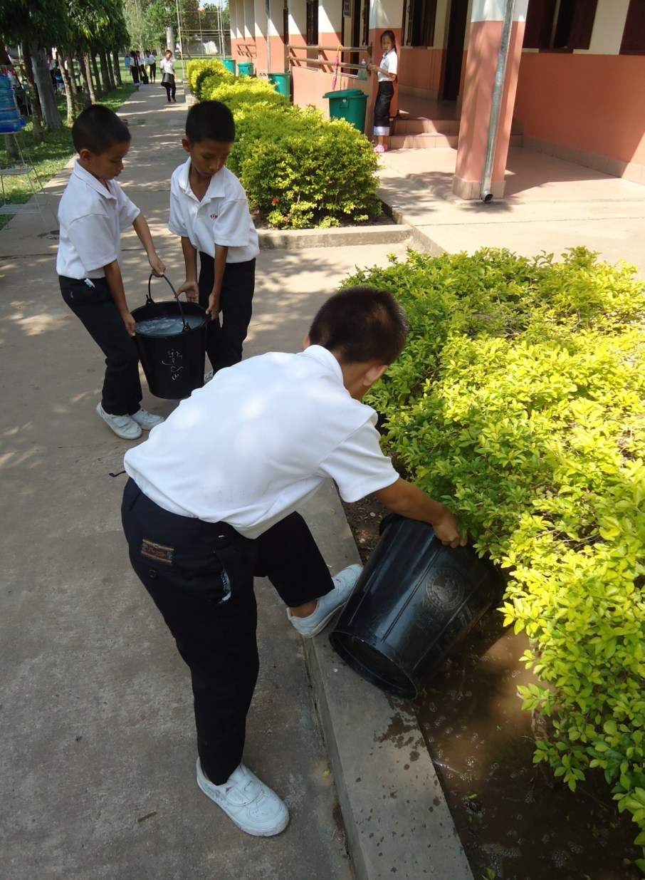 Some pupils water the plants with the retained water