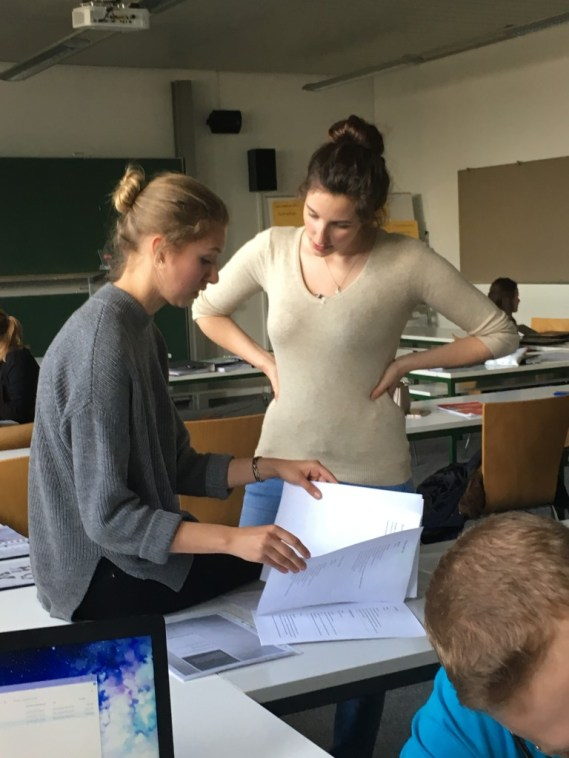 """Jana shows Team II's """"Games"""" workshop material to Ariane"""