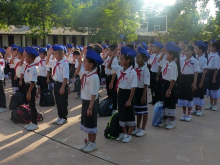 Primary schoolers salute while the flag is taken down