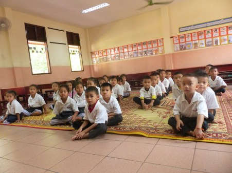 The children sit on the mat in an orderly fashion and wait for the teacher to start her lesson...