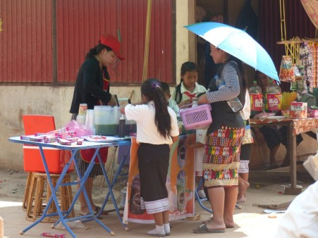 Some parents buy food for their children at the stalls in front of the school.