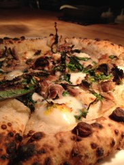 Antara pizza with duck confit, caramelized garlic, spigarello, chili & aceto balsamico.