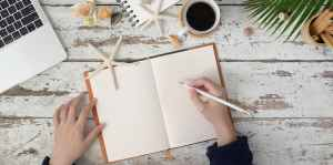 person holding white pencil writing on notebook