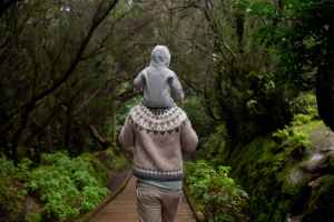 anonymous man with baby on shoulders walking away