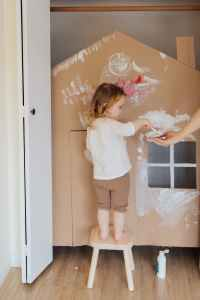 girl in white shirt and brown shorts standing in front of cardboard play house