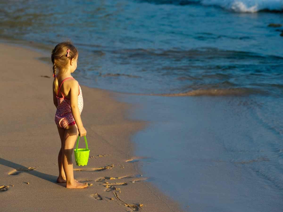girl holding bucket on seashore