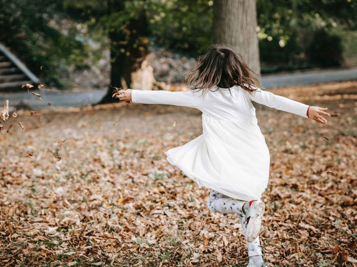 carefree girl spinning in park