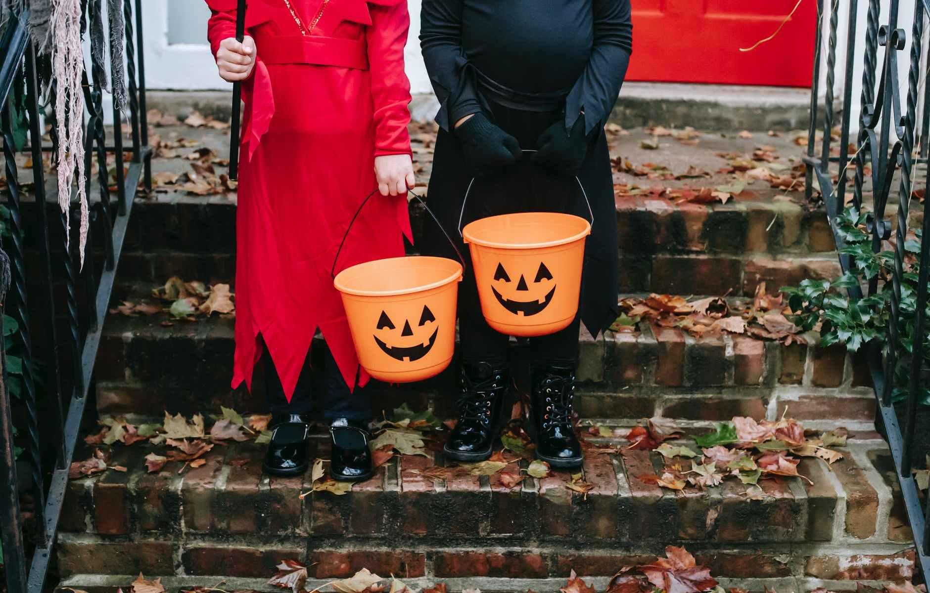 children holding a halloween design buckets