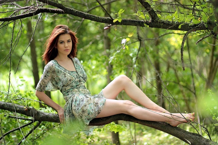 Lady with beautiful green dress sitting on a tree branch