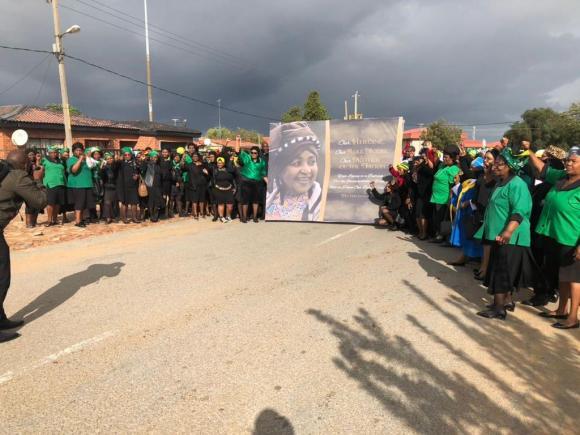 Women hold a huge potrait of Winnie Mandela in celebration of her life