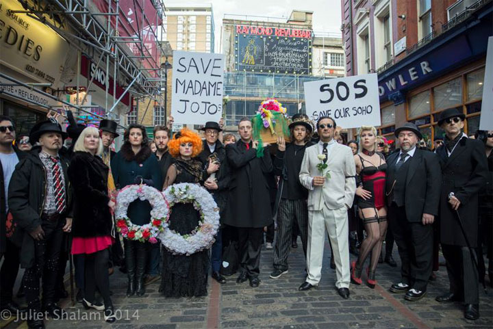 The London cabaret community gather with the coffin and banners across the street from Walker's Court and Madame Jojo's, with the Raymond Revue Bar neon sign above. ©Juliet Shalam