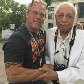 Tim Parker (USMC) & Wilk (Tuskegee Airman) embracing with tears rolling down their cheeks after exchanging a USMC coin.