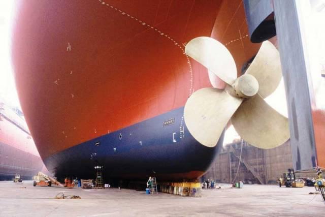 Vedle obřího lodního  šroubu největšího supertankeru světa TI OCEANIA, vypadají lidé jako mravenečci.