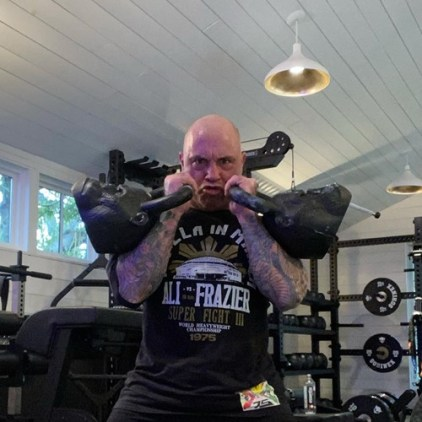 Joe Rogan working out with gorilla face-shaped kettlebells