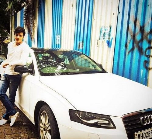 Aniruddh Dave posing with his car