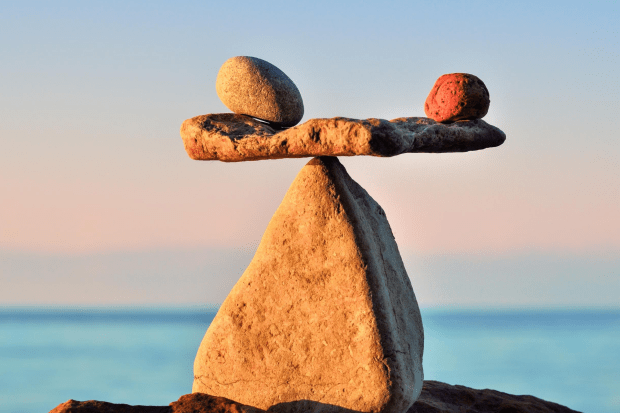 photo shows two rocks balanced on a flat rock on top of a triangular rock with water in the background