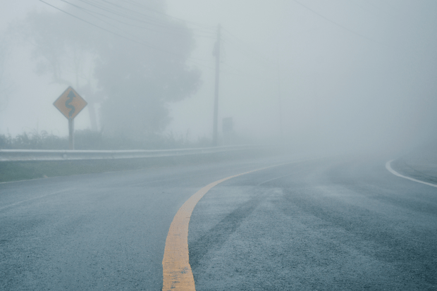 photo shows a foggy bend in a road