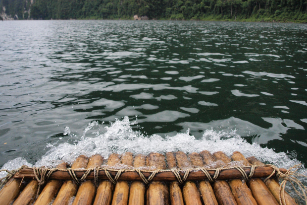 photo shows the front of a flat, wooden raft and the rushing water in front of it