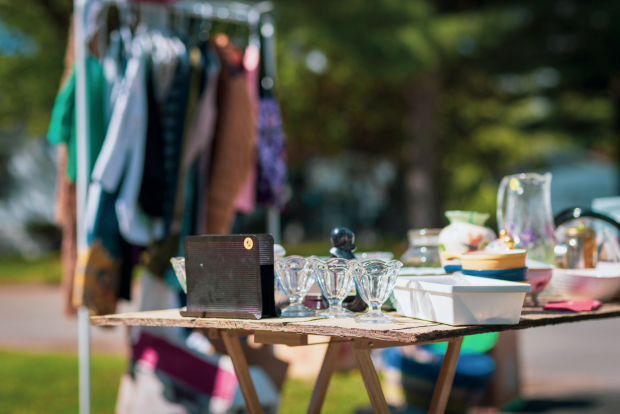 photo shows clothing hanging and a table full of glassware and kitchen goods for sale at a yard sale