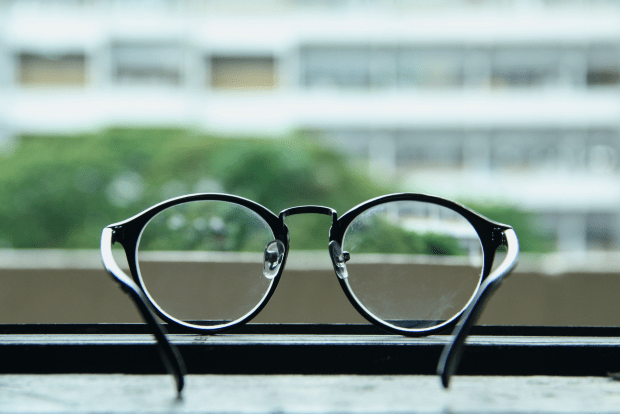 photo shows a pair of glasses aimed looking out an office window
